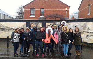Les lycéens posent devant les premiers murs peints rencontrés à Belfast ce matin.
